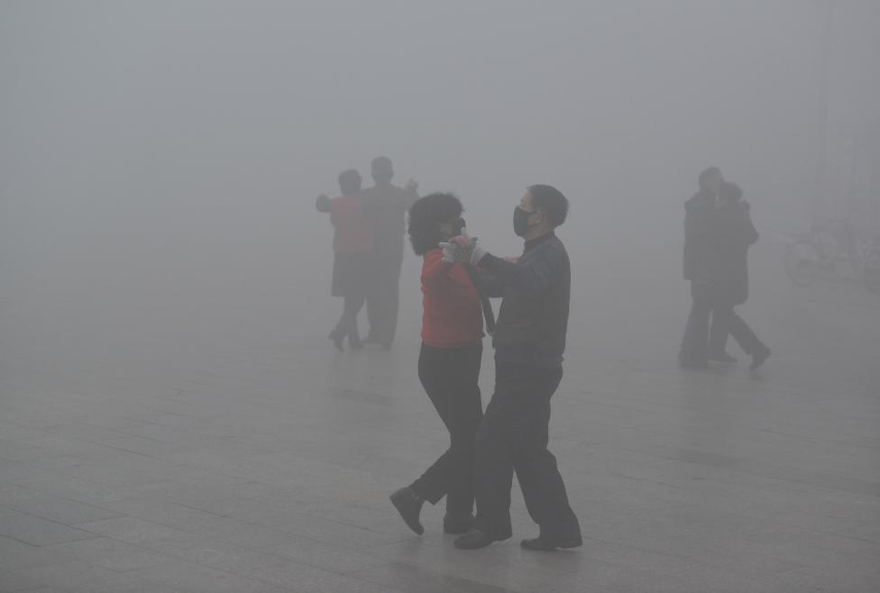 People wearing masks dance at a square among heavy smog during a polluted day in Fuyang