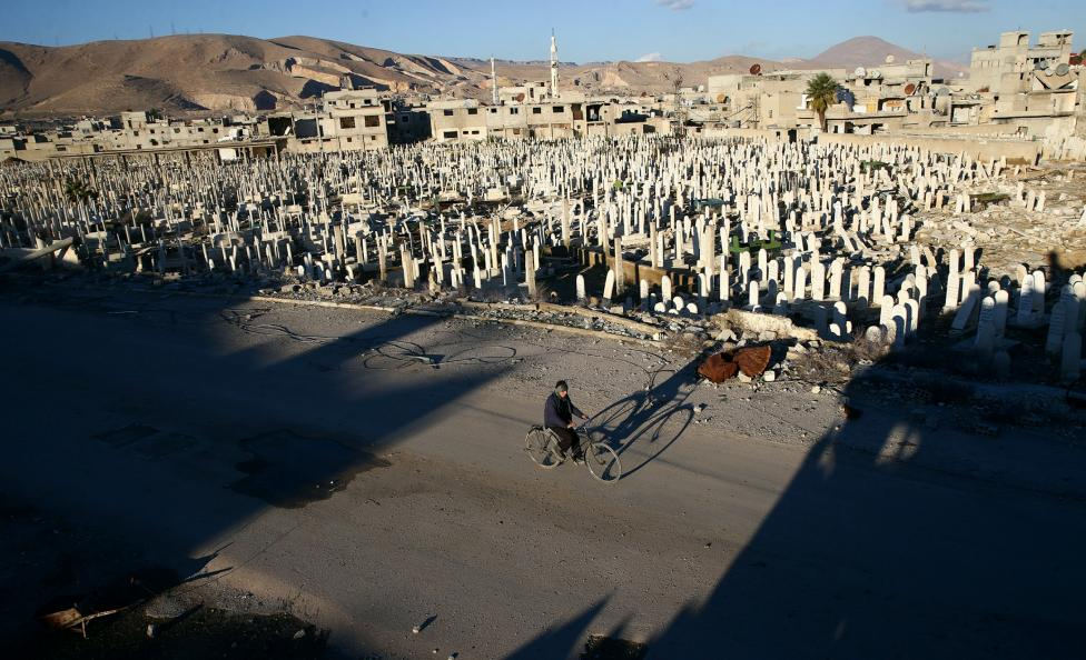 A civilian rides a bicycle past a cemetery in the rebel held besieged Douma neighbourhood of Damascus