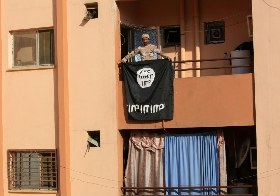 An Iraqi soldier holds an Islamic State flag from a building, during a battle with Islamic State militants in Al-shuqaq neighbourhood north of Mosul