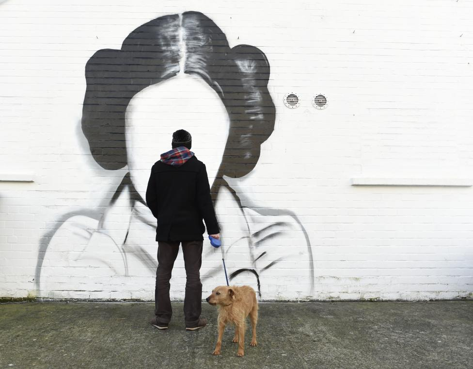 A man and his dog stop to look at a mural depicting Princess Leia from the film Star Wars played by Carrie Fisher in Belfast