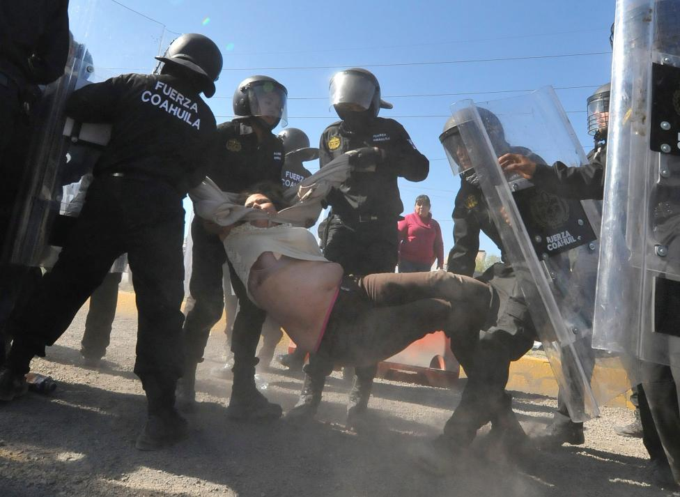 Policemen detain a demonstrator during a protest against the rising prices of gasoline enforced by the Mexican government, in Monclova