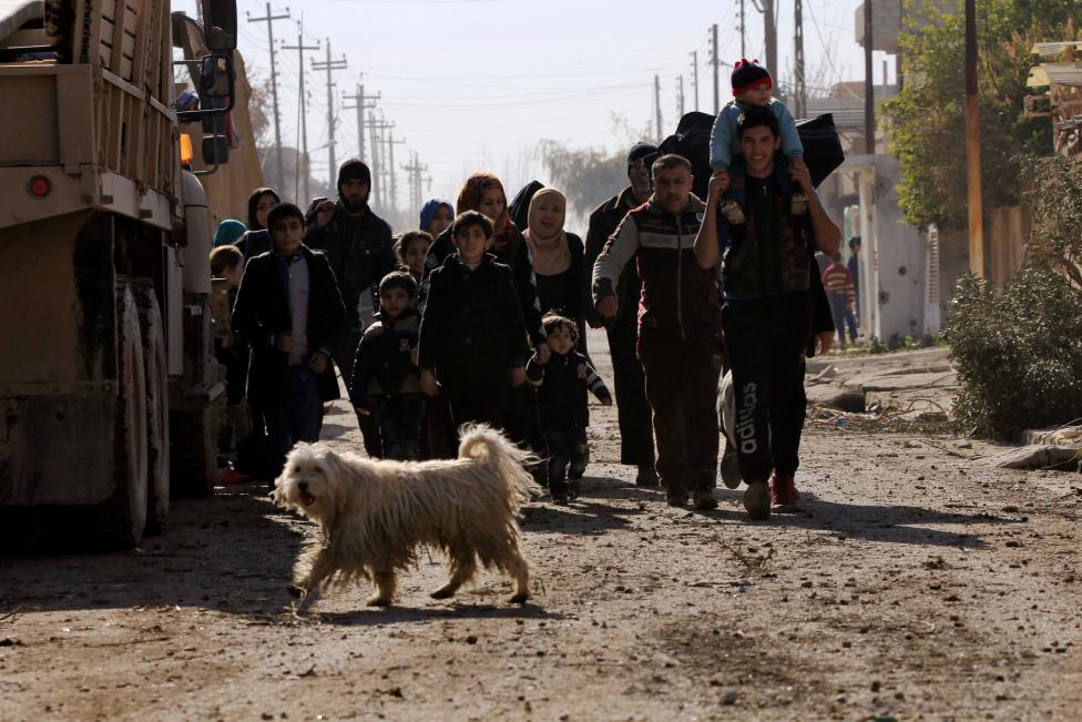 Iraqi people, who are fleeing from clashes, walk with their children during a battle with Islamic State militants, eastern Mosul