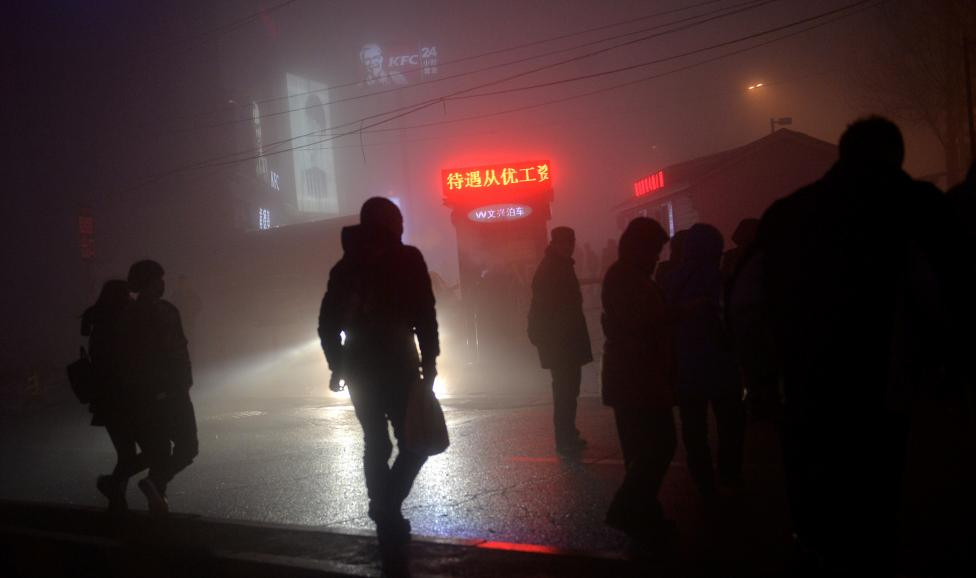 People are seen on a street in smog during polluted day in Shenyang, Liaoning province. REUTERS/Stringer