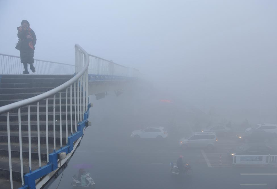 A woman walks past a bridge among heavy smog during a polluted day in Fuyang, Anhui province. China Daily
