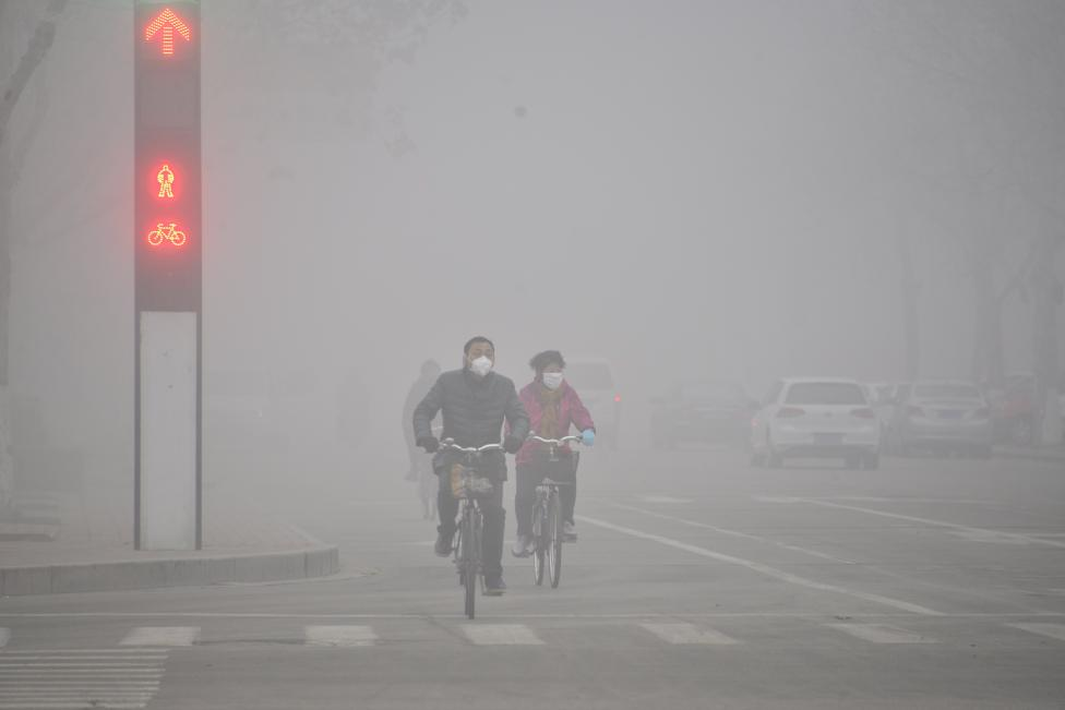 People wearing masks ride bicycles across a street in smog in Liaocheng, Shandong province. REUTERS/Stringer