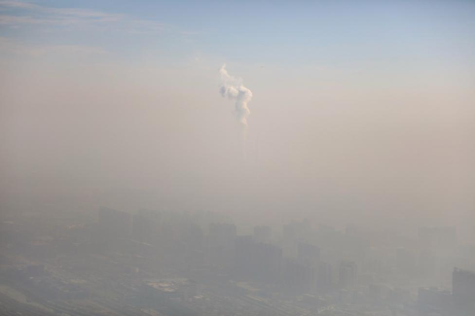 A chimney of a power plant is pictured among smog as a red alert for air pollution is issued in Beijing. REUTERS/Stringer