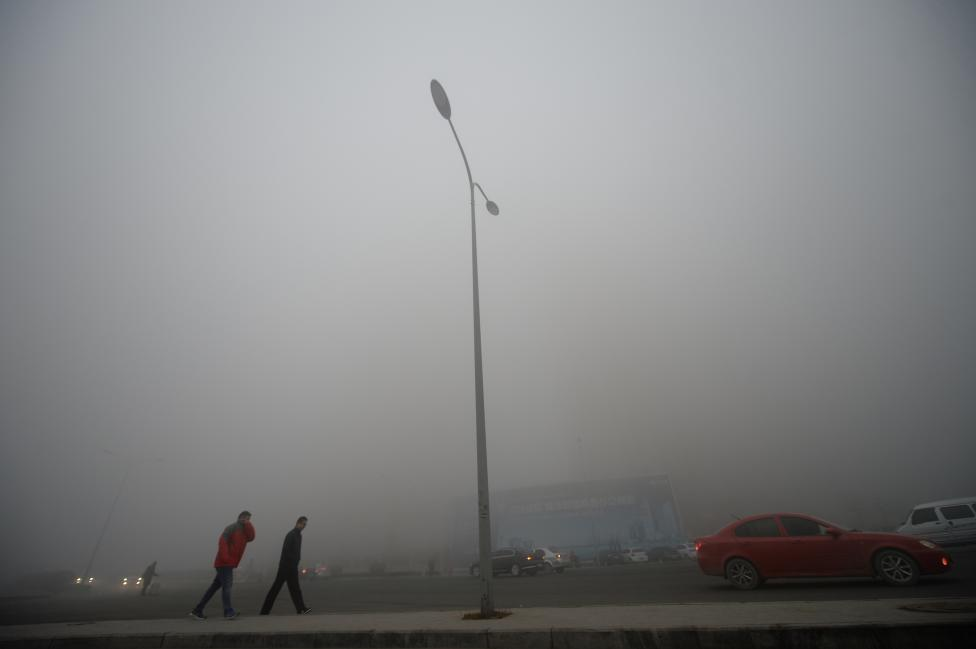 People walk in heavy smog during a polluted day in Jinan, Shandong province. REUTERS/Stringer
