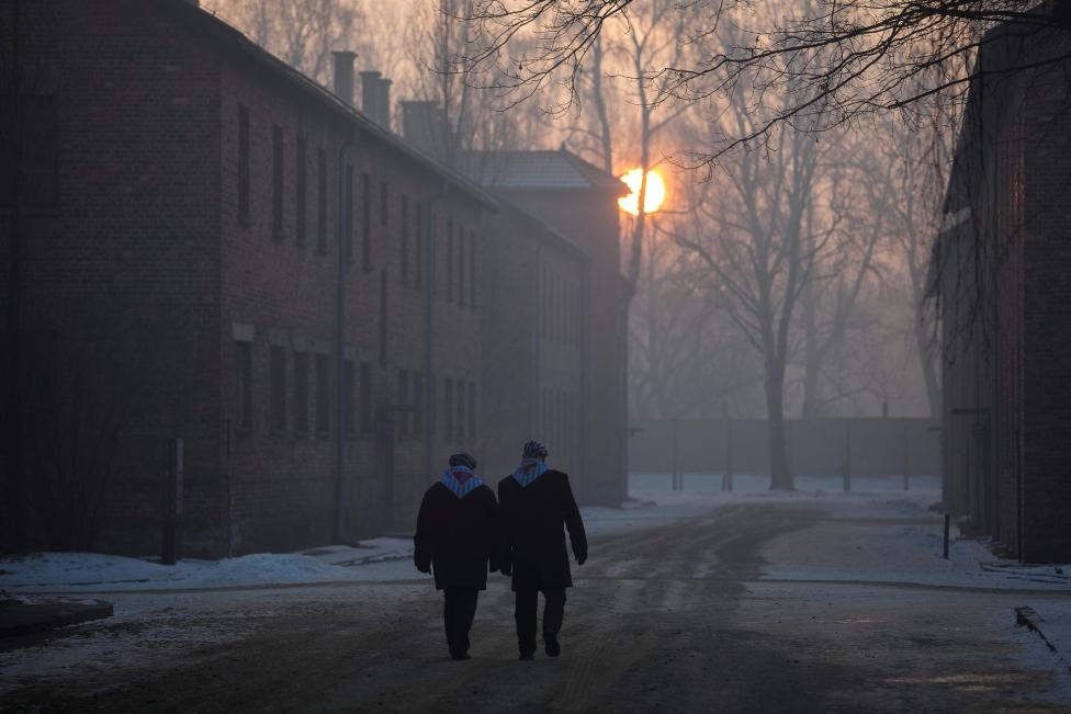 Survivors walk in the former Nazi German concentration and extermination camp Auschwitz-Birkenau in Oswiecim