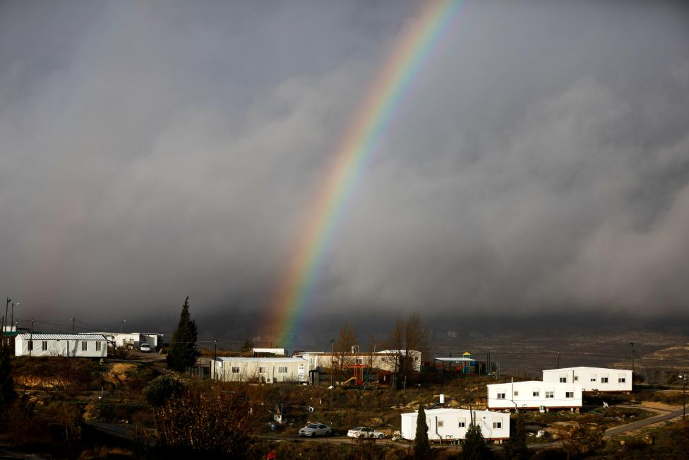 A rainbow is seen over the Israeli settler outpost of Amona in the occupied West Bank