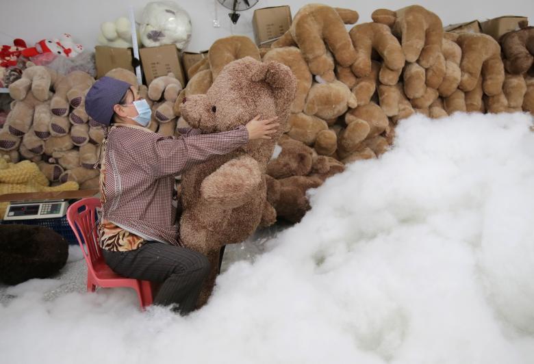 Работница набивает мягкие игрушки на фабрике в Ухане в провинции Хубэй.