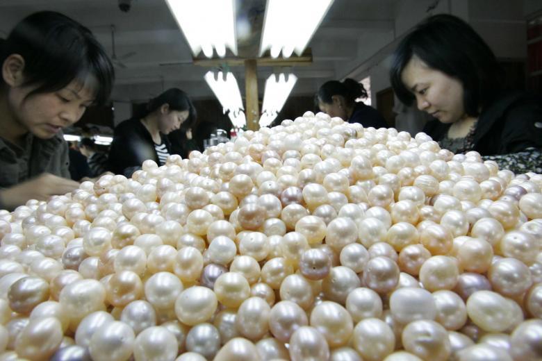 Работницы сортируют искусственный жемчуг на фабрике по его производству в провинции Чжэцзян.