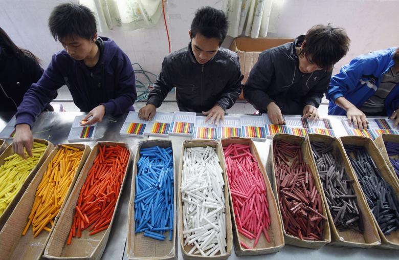 Рабочие-мигранты фасуют мелки на игрушечной фабрике в Дунгуане в провинции Гуандун.