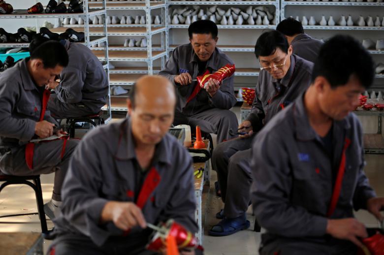 Рабочие из Северной Кореи изготавливают футбольные бутсы на фабрике в Даньдуне.