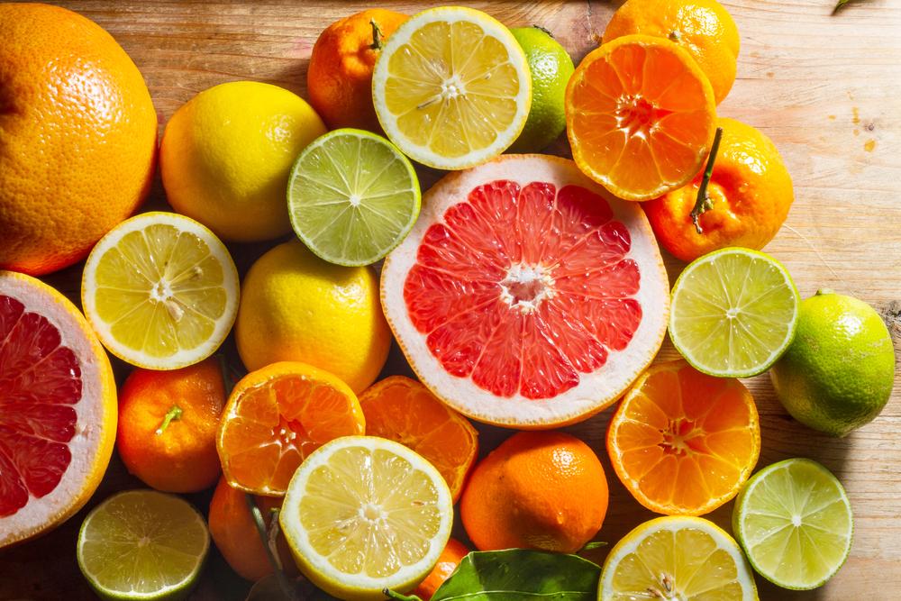 Fresh, juicy, zesty citruis fruits: lemons, limes, grapefruit, clementines. Against wooden background.