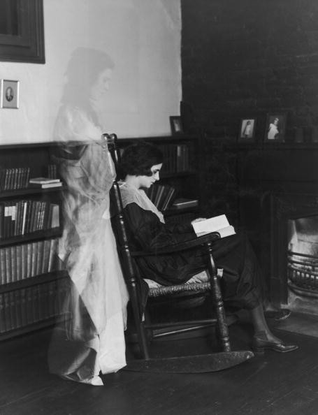 A ghostly apparition appears behind a young woman, who sits reading, oblivious to her spectral companion, circa 1925. (Photo by FPG/Hulton Archive/Getty Images)