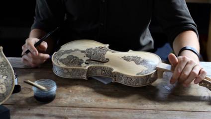 Художник дополняет красоту скрипок и виолончелей, расписывая их вручную