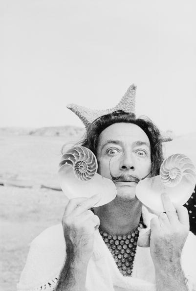 Spanish surrealist artist Salvador Dali (1904 - 1989) holds up two seashells at his home in Cadaques on the Costa Brava, Spain, 8th January 1955. Original Publication : Picture Post - 7465 - A Day With Salvador Dali - pub. 1955 (Photo by Charles Hewitt/Picture Post/Hulton Archive/Getty Images)