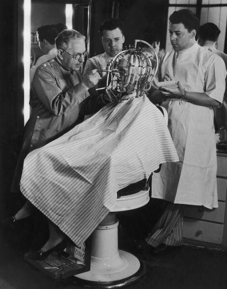 Hollywood cosmetics expert Max Factor (1877 - 1938, left) takes precise measurements of a young woman's head and face with a 'Beauty Calibrator', device, circa 1932. The device is intended to detect subtle facial characteristics, which need to be disguised or enhanced for the screen with make up. (Photo by FPG/Hulton Archive/Getty Images)
