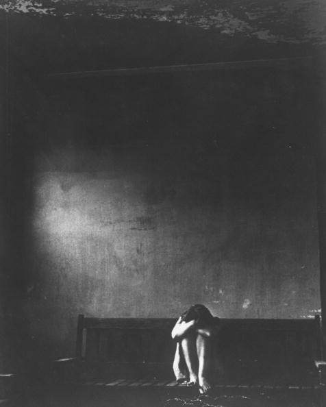 Barefoot female mental patient suffering fr. withdrawal w. her head buried in her arms as she hugs her knees while sitting in the middle of a long wooden bench against a starkly dark wall in an insane asylum.  (Photo by Jerry Cooke/The LIFE Picture Collection/Getty Images)