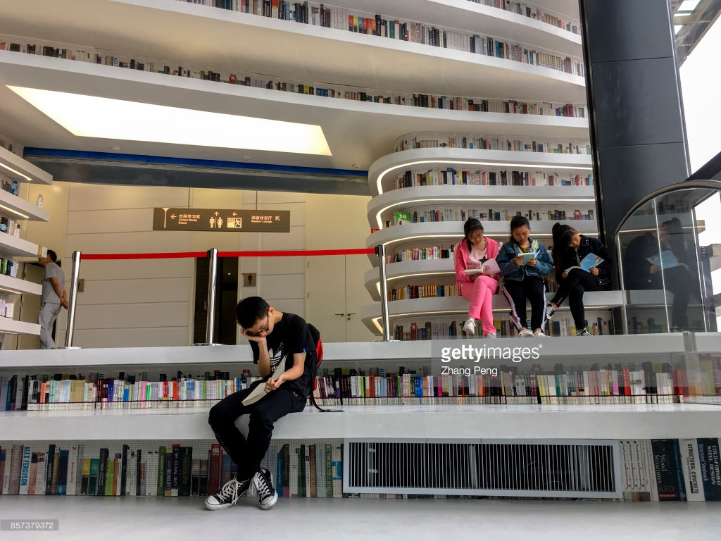 "TIANJIN, CHINA - 2017/10/02: Readers in the library.  The Binhai new area library, opened in the National day, also called ""the eye of Binhai"", located in the cultural center of Binhai new area,  is a new cultural landmark and travel destination. (Photo by Zhang Peng/LightRocket via Getty Images)"