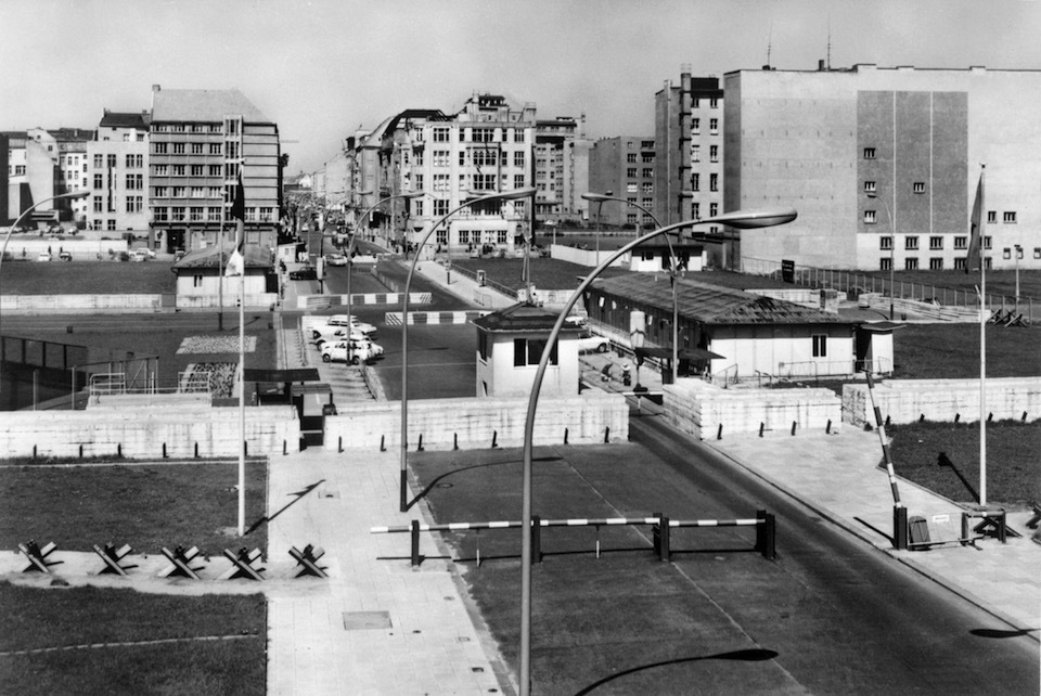 "Picture dated March 1965 of ""Checkpoint Charlie"" crossing point, the only one in the Berlin Wall between East (Soviet sector, background) and West (American sector) Berlin used only by the foreigners. The Berlin concrete wall was built by the East German government in August 1961 to seal off East Berlin from the part of the city occupied by the three main Western powers. Built largely to prevent mass illegal immigration to the West which was threatening the East German economy. The wall, built along the border between German Democratic Republic (GDR) and Federal Republic of Germany, was the scene of the shooting of many East Germans who tried to escape from GDR. The two countries remained divided until November 1989 when the wall was unexpectedly opened following increased pressure for political reform in GDR. Later it was taken down."