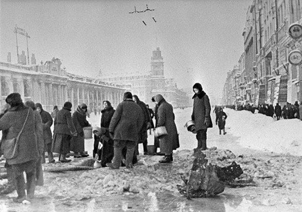 Жители блокадного Ленинграда набирают воду, появившуюся после артобстрела в пробоинах в асфальте, декабрь 1941 года