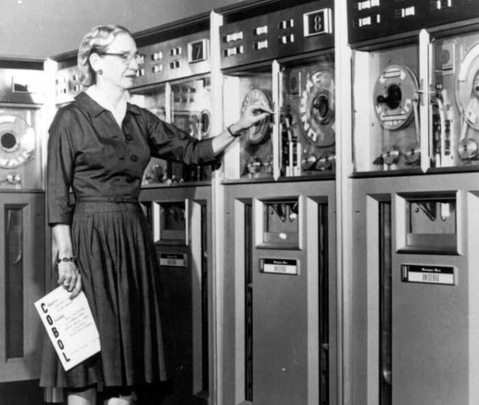 """""""A publicity shot of Grace Hopper advertising the Common Business Oriented Language (COBOL), a more user-friendly computer language, 1952. Grace Murray Hopper (December 9, 1906 - January 1, 1992) was an American computer scientist and United States Navy rear admiral. A pioneer in the field, she was one of the first programmers of the Harvard Mark I computer, and invented the first compiler for a computer programming language. She popularized the idea of machine-independent programming languages, which led to the development of COBOL, one of the first high-level programming languages. She is credited with popularizing the term """"""""debugging"""""""" for fixing computer glitches (inspired by an actual moth removed from the computer). She was awarded 40 honorary degrees from universities worldwide during her lifetime. Owing to the breadth of her accomplishments and her naval rank, she is sometimes referred to as """"""""Amazing Grace"""""""". She died in in 1992 at the age of 85 and was interred with full military honors in Arlington National Cemetery."""""""