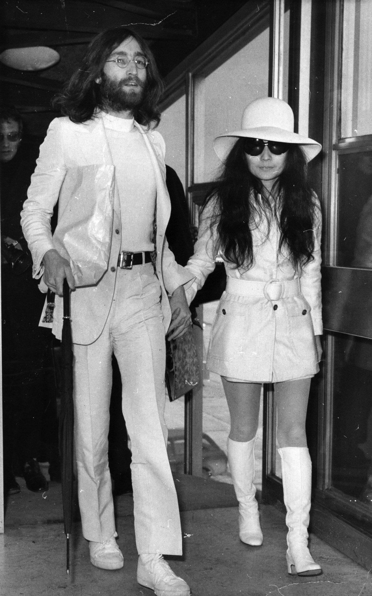 2nd April 1969:  Singer and songwriter John Lennon (1940 - 1980) and his wife artist Yoko Ono, both dressed in white at London Airport.  (Photo by Evening Standard/Getty Images)