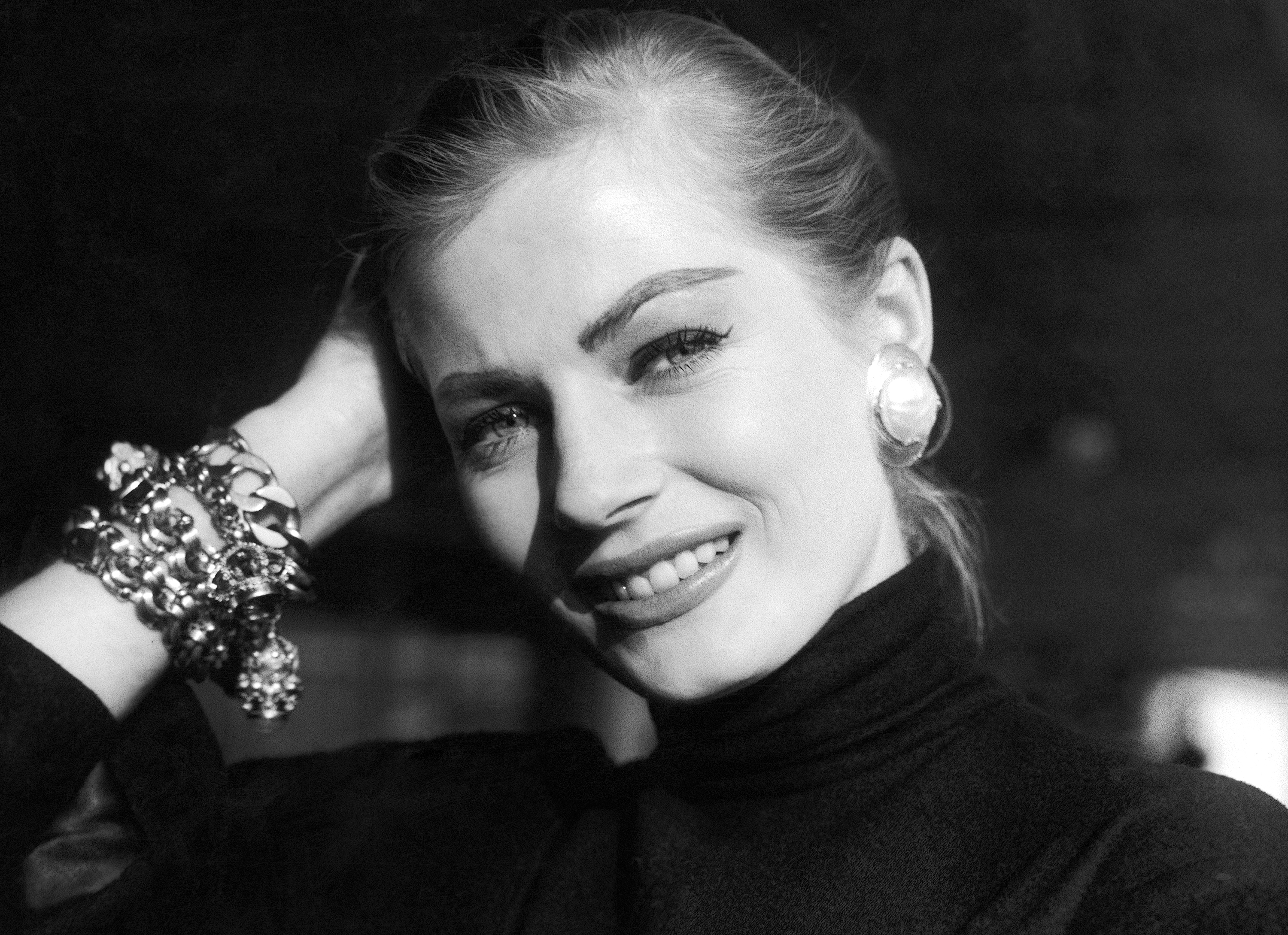 "Portrait of Swedish actress Anita Ekberg, a former ""Miss Sweden,"" taken at her arrival at London, United Kingdom, airport from Stockholm on Nov. 15, 1955 to take part in a film with Victor Mature, Michael Wilding and Eunice Gayson (""Zarak Khan""). ""I've finished with pin-up photos,"" she told cameramen at the airport who asked her to take her coat off. She wears pearl and gold ear-rings, a gold bracelet with charms and a tight-fitting coat of black wood. (AP Photo)"