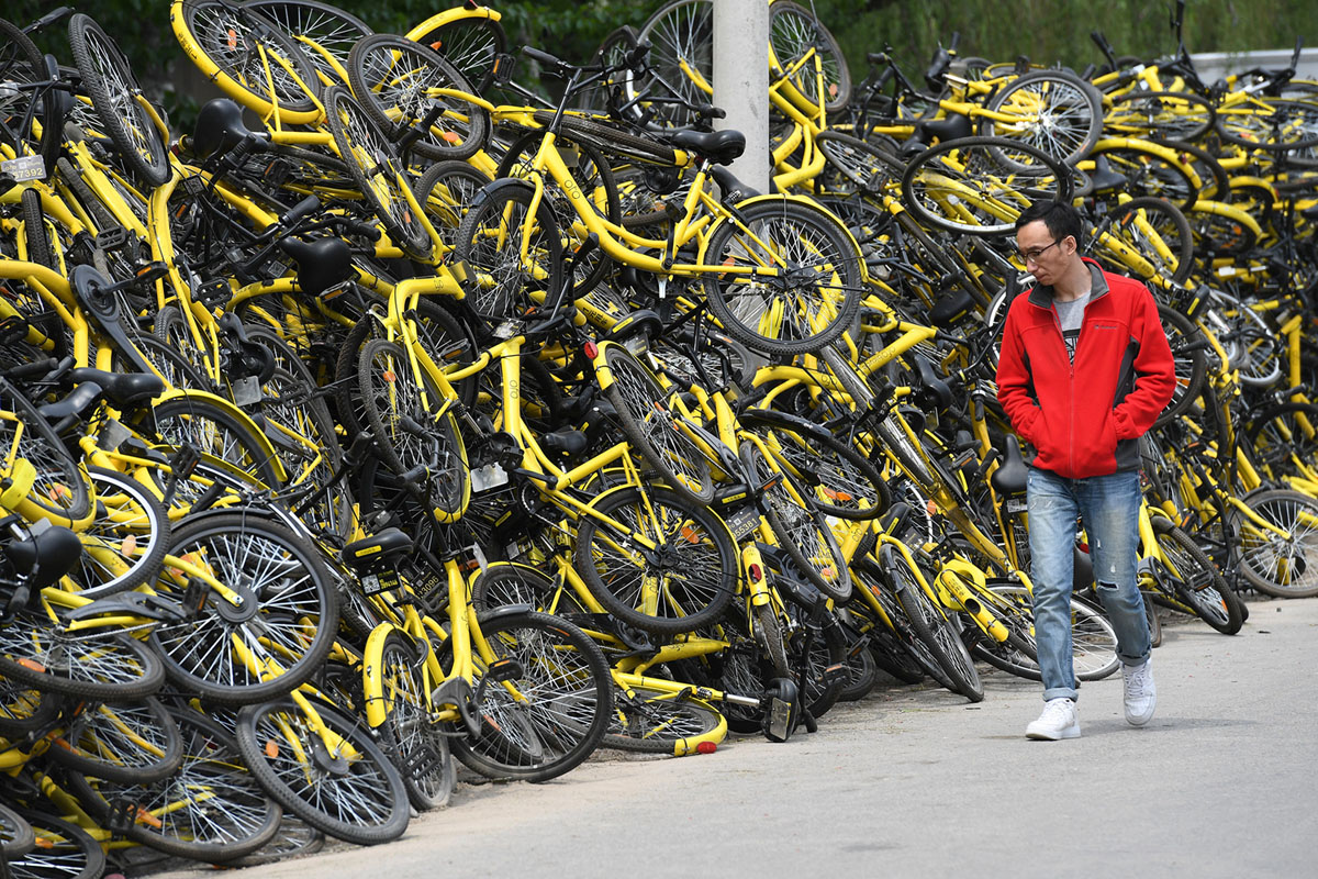 A man walks past shared bikes placed at a repair factory in Beijing