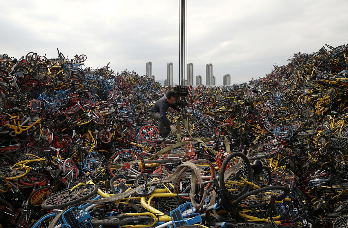 A worker untangles a rope amid piled-up shared bicycles at a vacant lot in Xiamen, Fujian province, China December 13, 2017. Picture taken December 13, 2017. REUTERS/Stringer  ATTENTION EDITORS - THIS IMAGE WAS PROVIDED BY A THIRD PARTY. CHINA OUT. - RC1E8FA5CB40