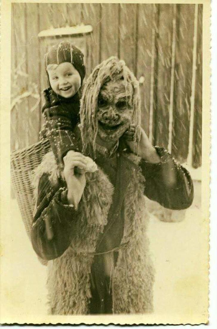 Мальчик катается на мужчине, одетом как демон для парада Крампусов