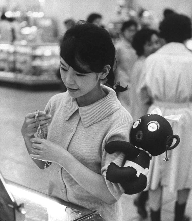 Женщина носит игрушку Dakko-chan на руке. Япония, 1960 год