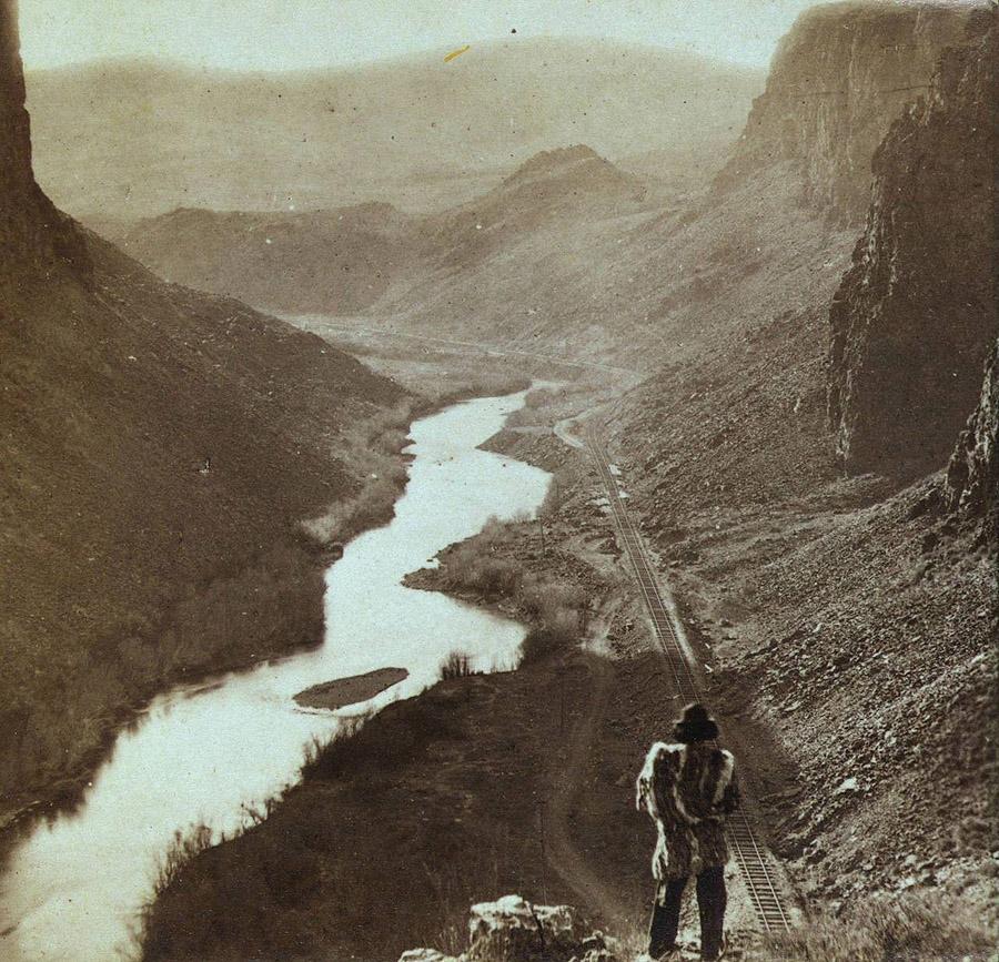 Коренной житель Америки смотрит вниз на только что построенный участок трансконтинентальной железной дороги, Невада, примерно 1868 год