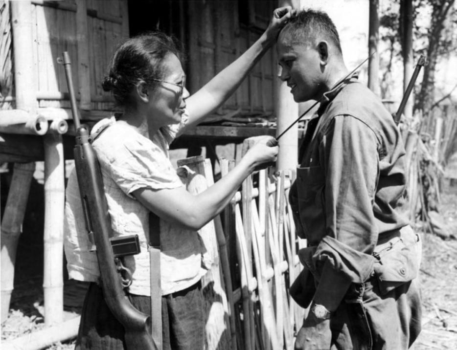 Филиппинская партизанка Нивес Фернандес показывает американскому солдату, как она убивала японских солдат во время оккупации. 1944 год