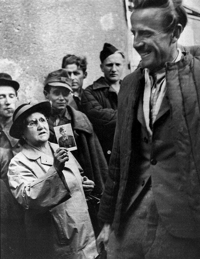Мать показывает фотографию своего сына возвращающимся военнопленным, пытаясь отыскать его. Вена, 1947 год