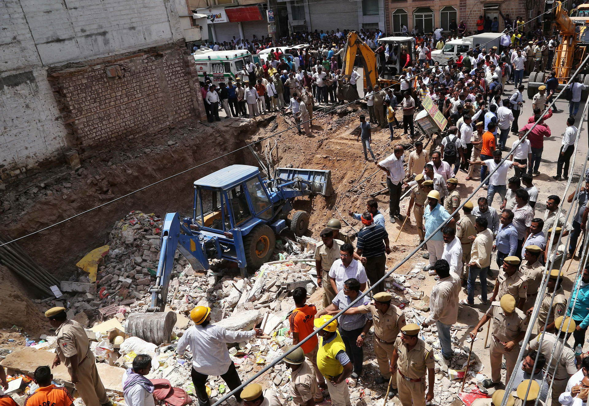 Police and rescue workers look for survivors amidst the rubble at the site of a collapsed building in Jodhpur