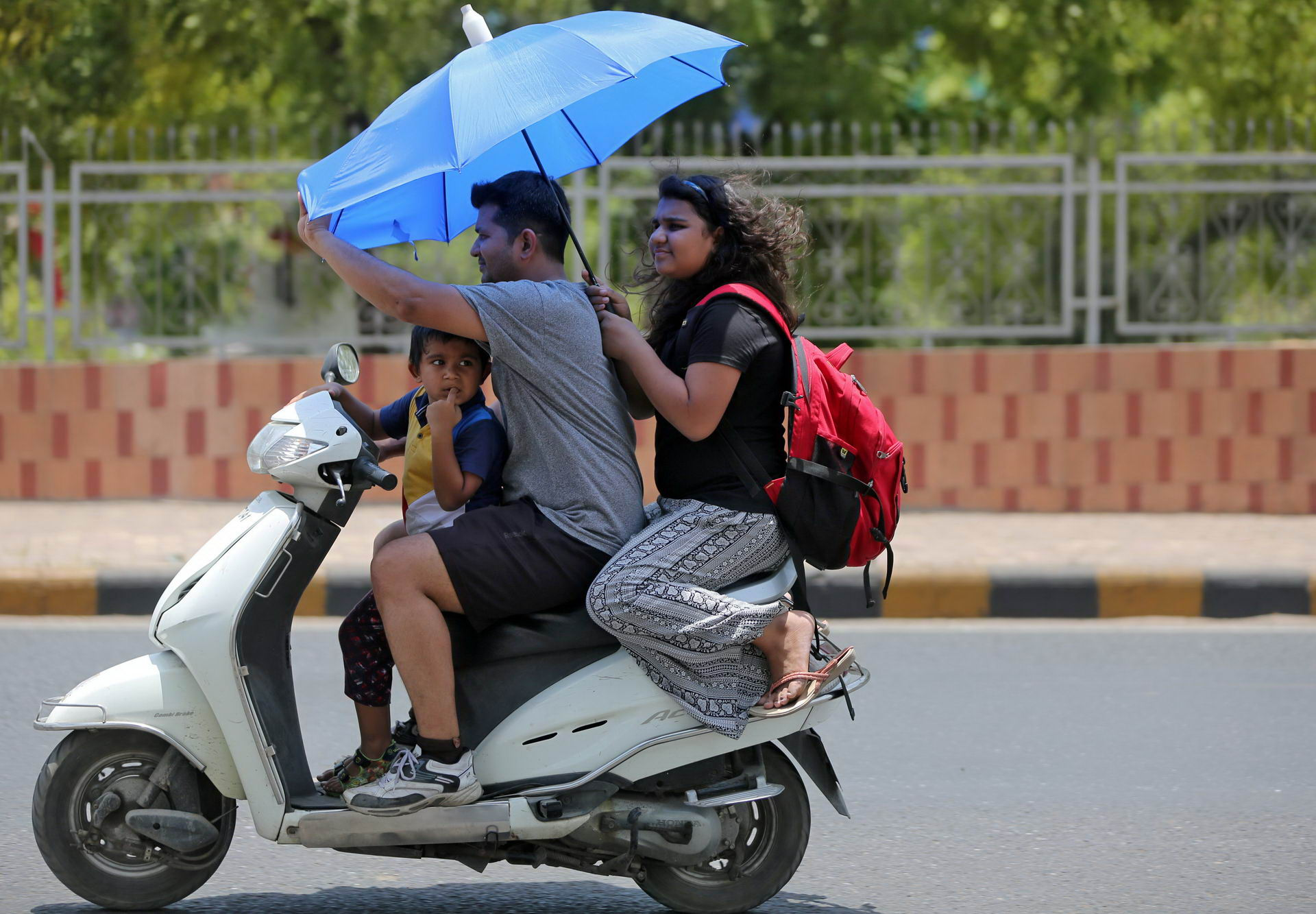 Scooterist covers himself with an umbrella to protect from heat on a hot day in Ahmedabad