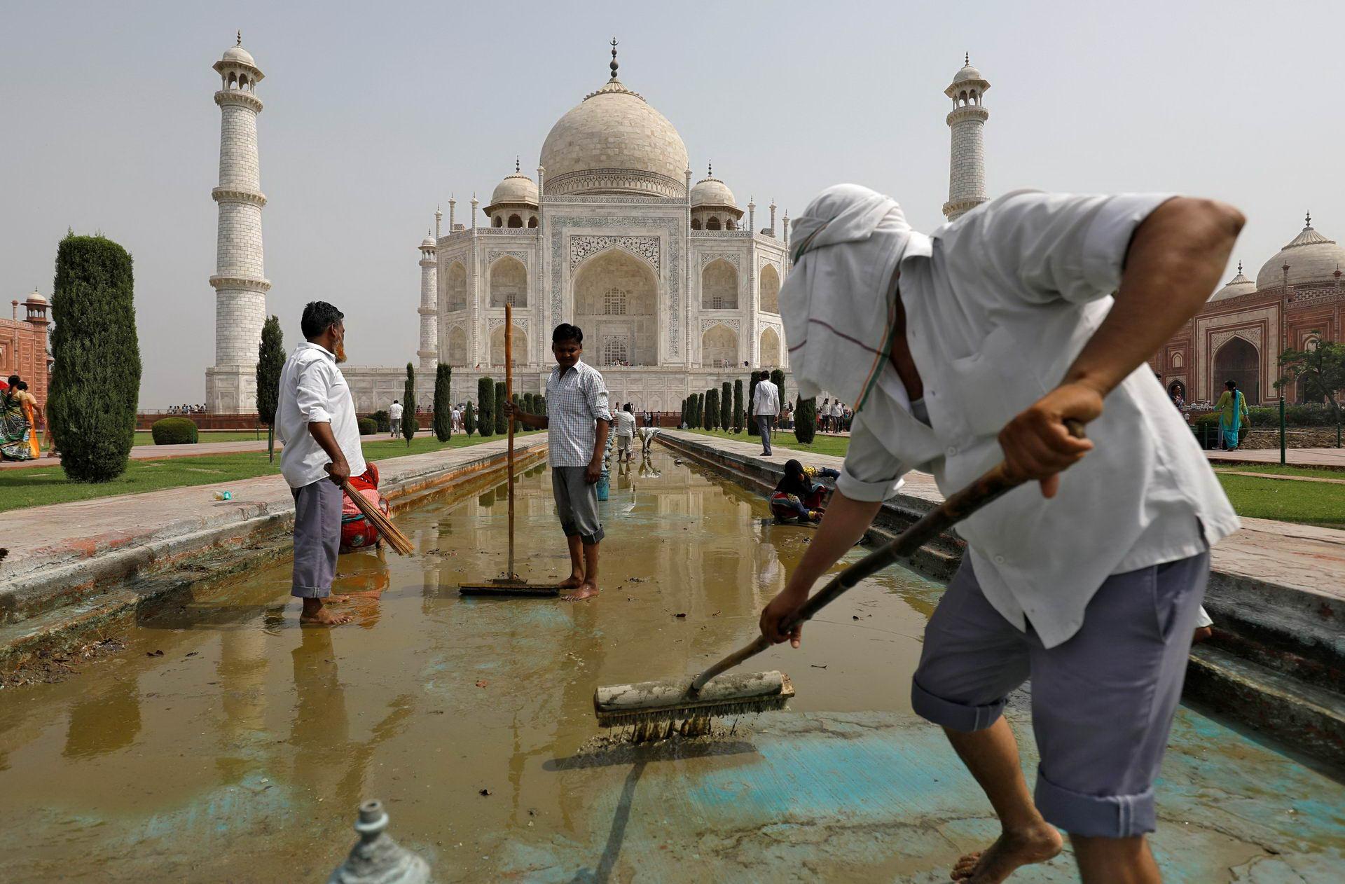 Labourers clean the fountain in the historic Taj Mahal premises in Agra