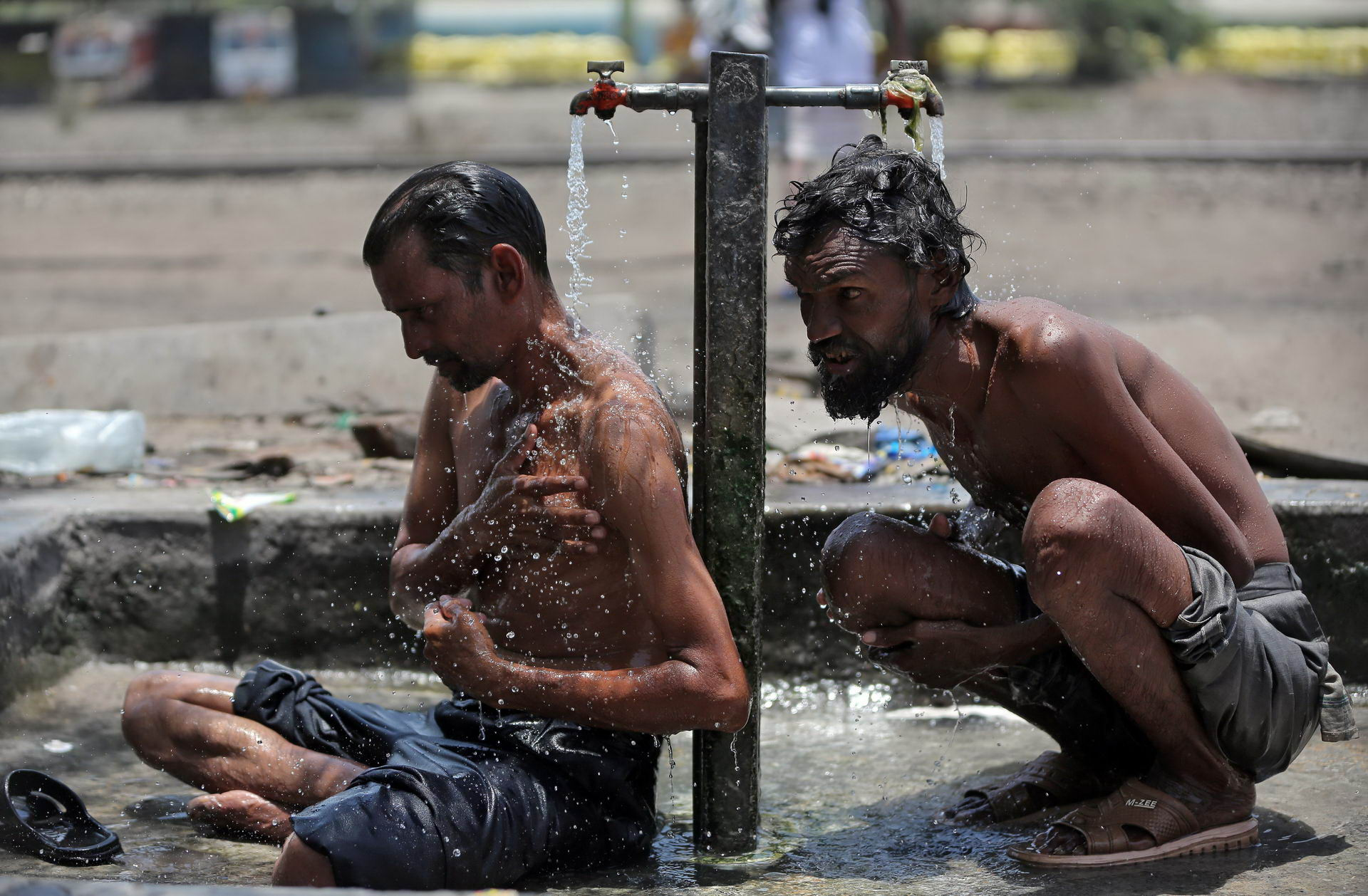 Men bathe at municipal taps along railway tracks in Ahmedabad