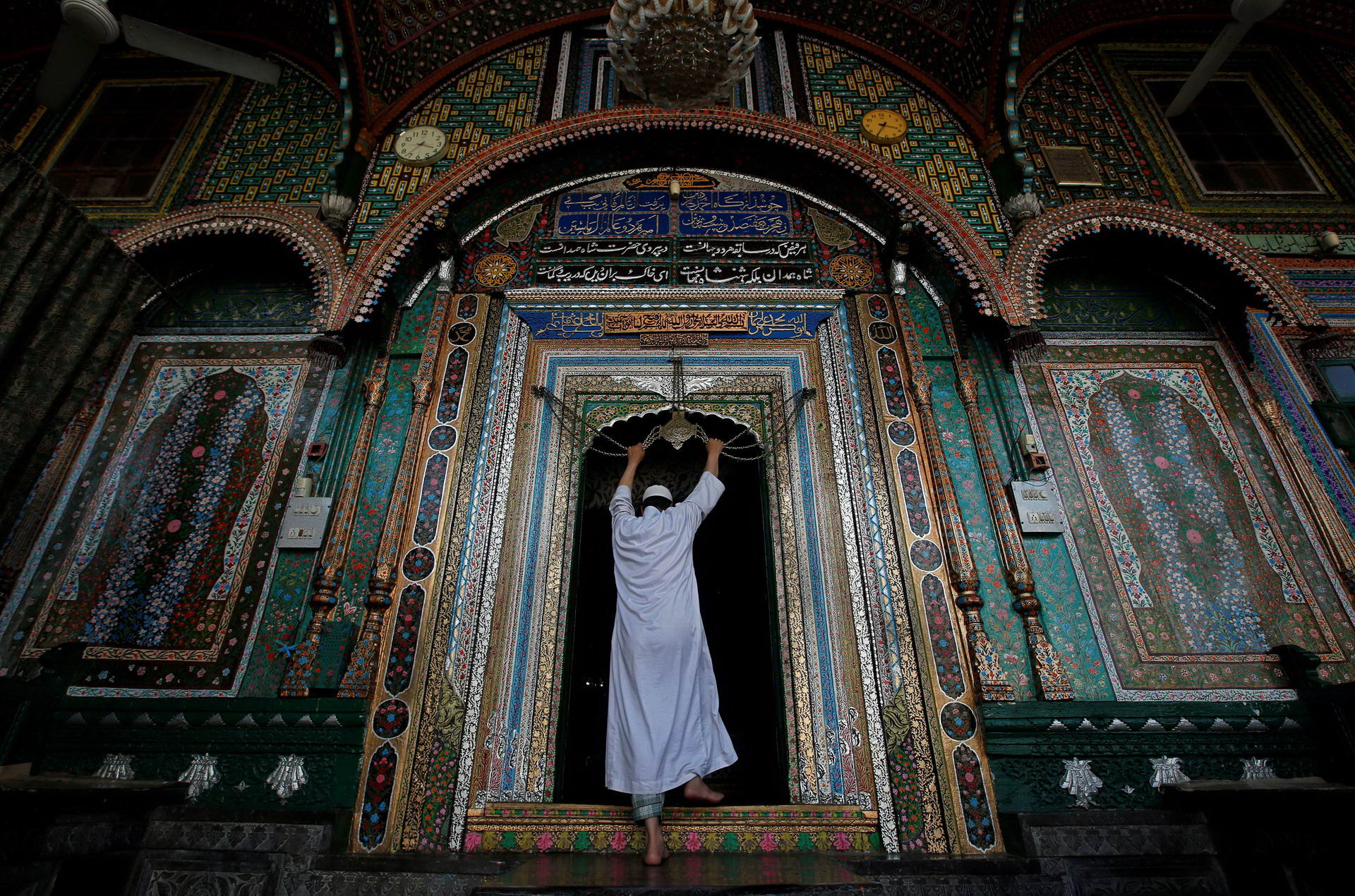 A Muslim man touches an ornament, engraved with verses from the Koran, tied to a chain at shrine of Mir Syed Ali Hamdani during holy month of Ramadan in Srinagar