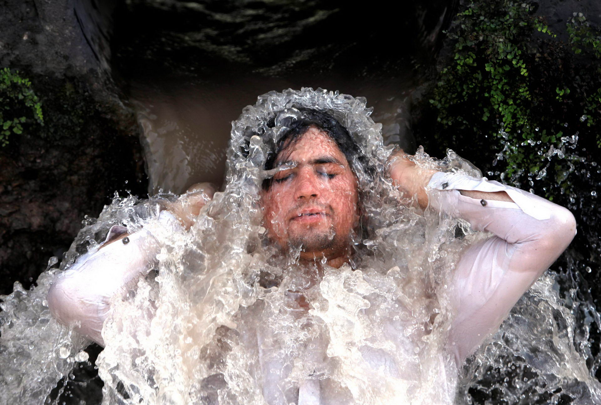 A man reacts as he cools off from the hot and sunny weather, under a water pipe from a canal on the outskirts of Peshawar