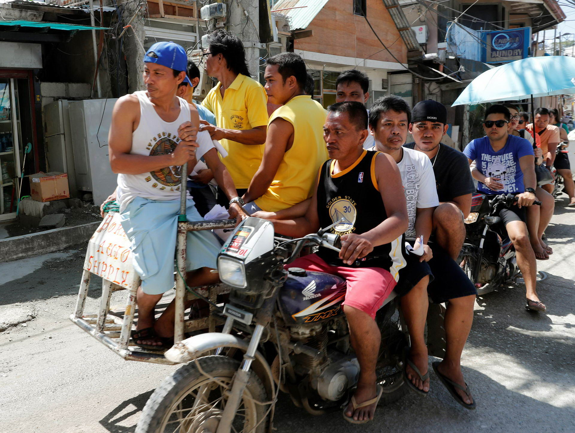 Workers who were cut off from their jobs due to the temporary closure of the holiday island Boracay, ride on a tricycle in the Philippines