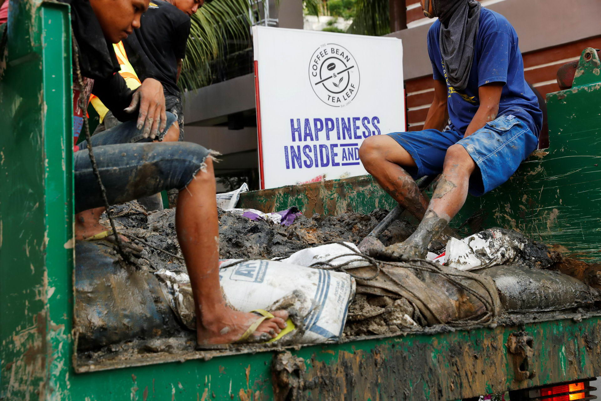 Filipino workers ride in a truck with waste materials collected from clogged sewage drainage pipes from the main road of Boracay island