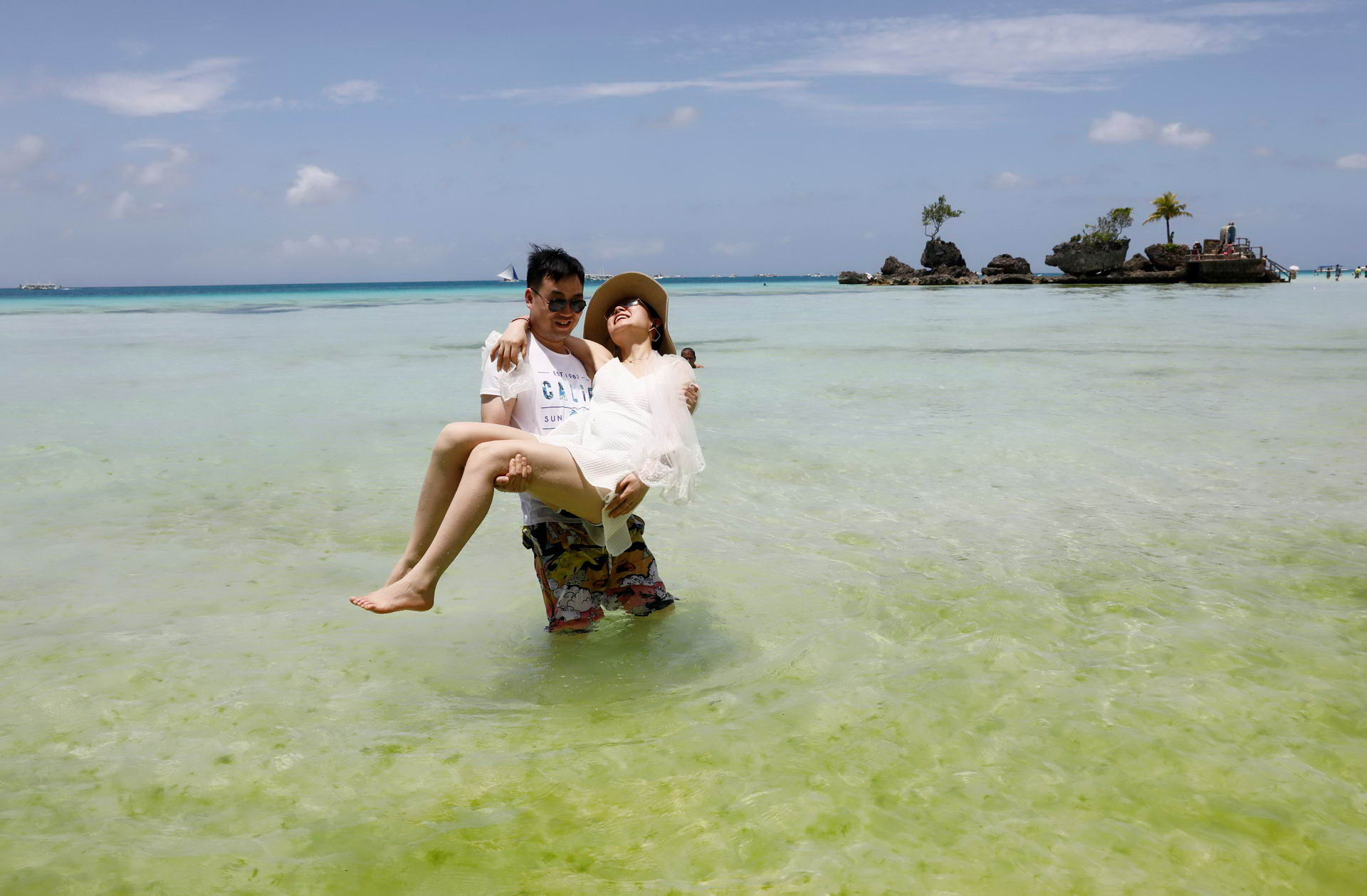 Newly-wed Chinese tourists frolic in the beach of Boracay