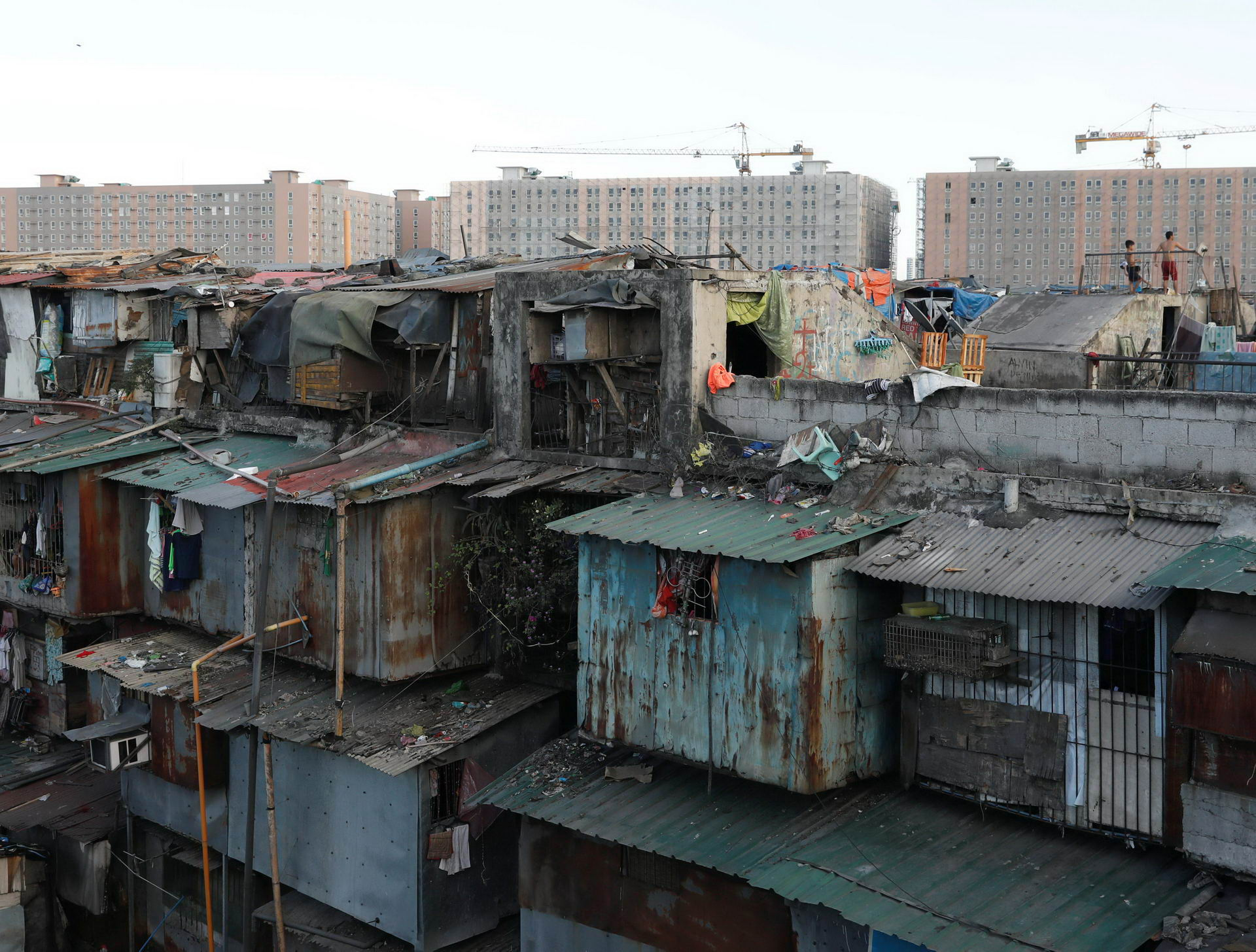 Residents stand on a rooftop of a shanty tenement house while newly-built condominium buildings are seen in the background in Tondo district, metro Manila