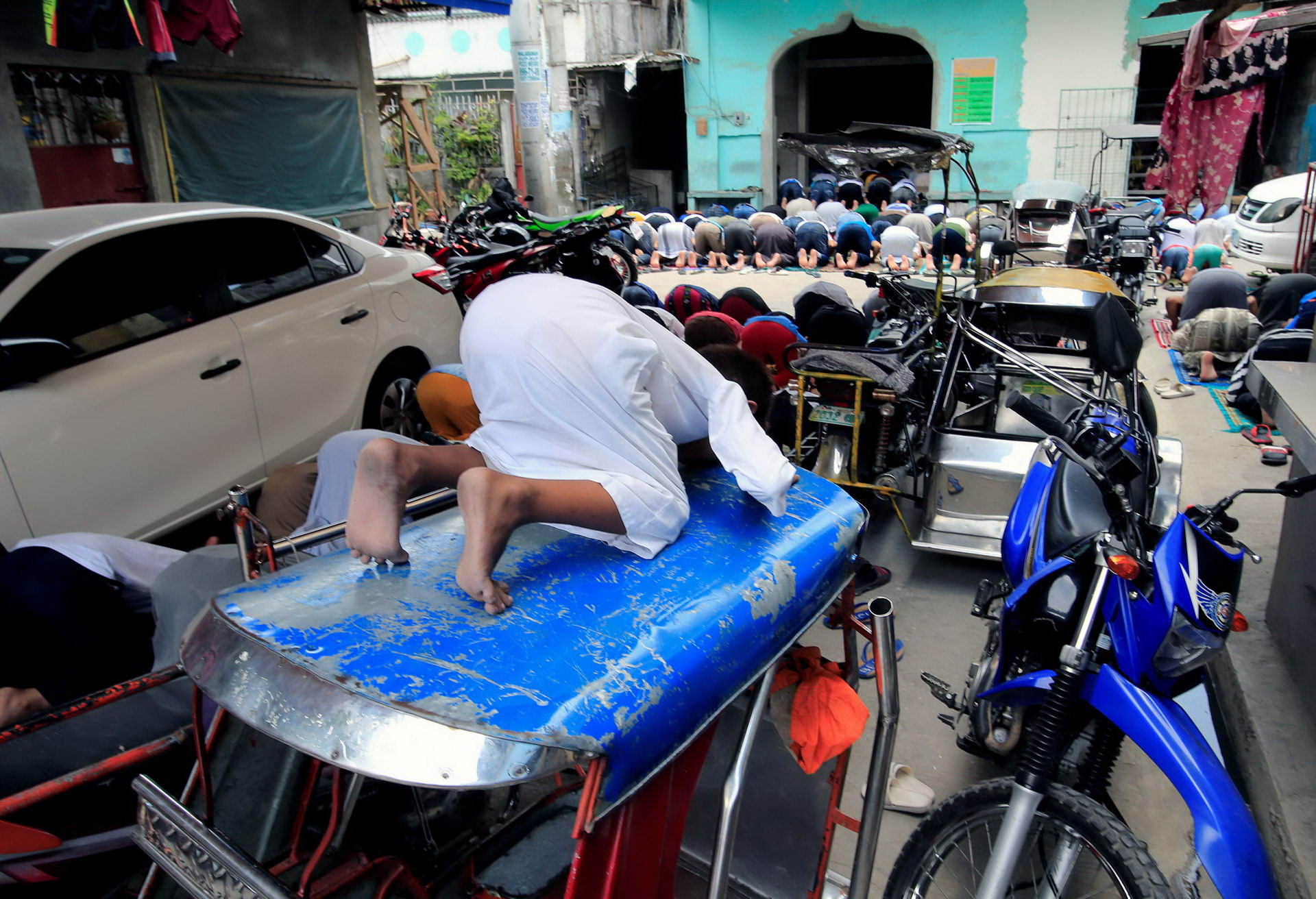 Filipino Muslims pray during the second day of Ramadan outside a mosque in Baseco, Tondo city, metro Manila