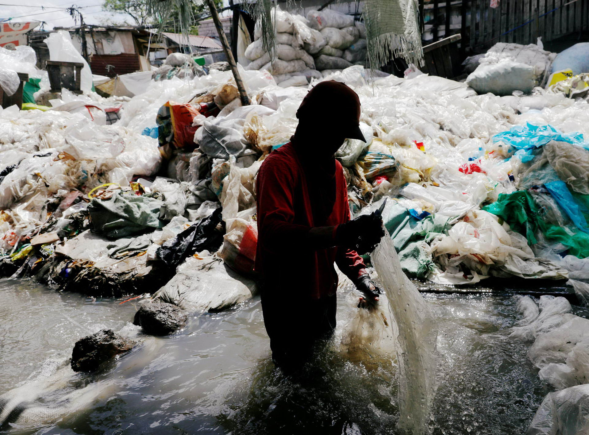 A man washes plastic for recycling in a murky pond