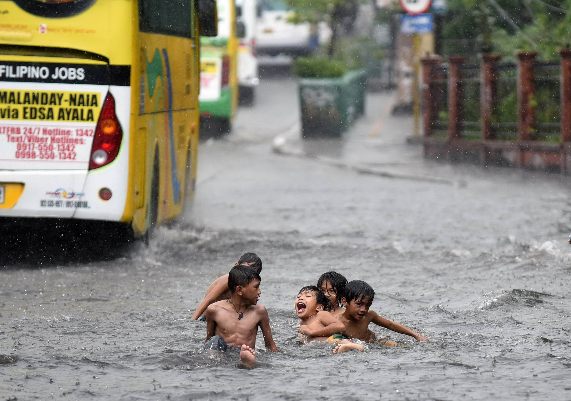 Children play on a flooded highway during a summer downpour in Edsa