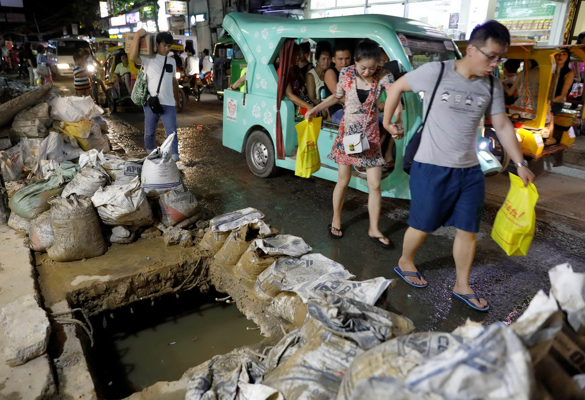 Tourists walk past a clogged sewer and uncollected sacks containing waste from the sewers along a road at Boracay